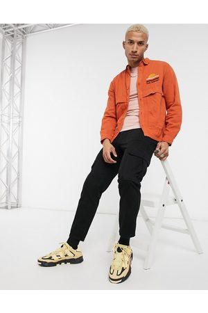 ASOS Twill overshirt in orange with sunset chest embroidery-Brown