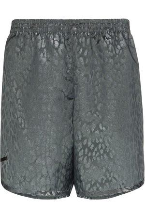 TRUE TRIBE Metallic sheen leopard print swim shorts